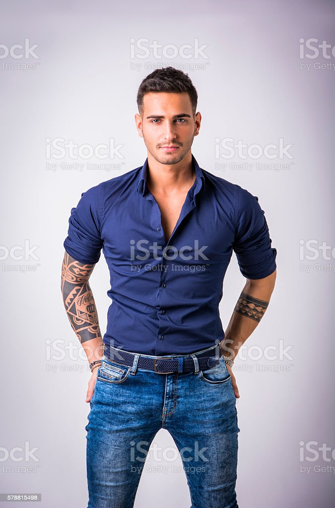 Young man in blue shirt and jeans isolated stock photo