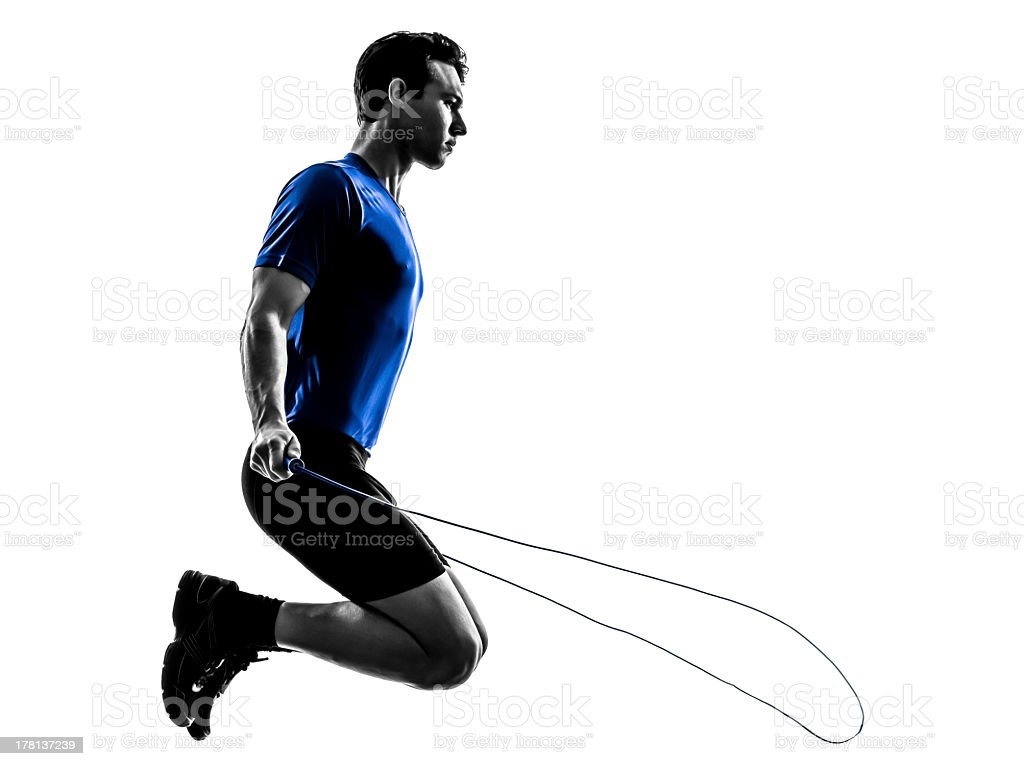 Young man in blue shirt jump roping at apex of jump stock photo