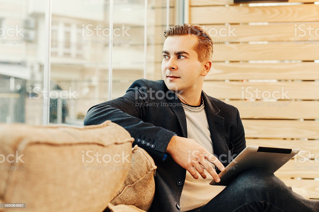 Young man in caffe holding digital tablet stock photo