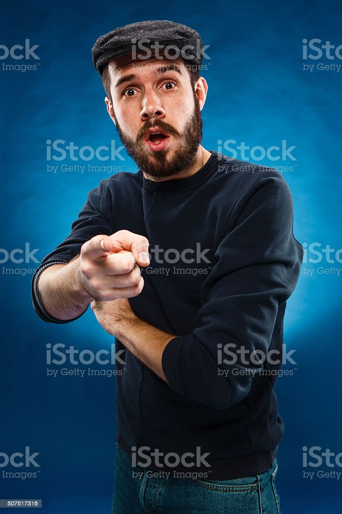 Young man in cap, finger pointing towards the camera stock photo