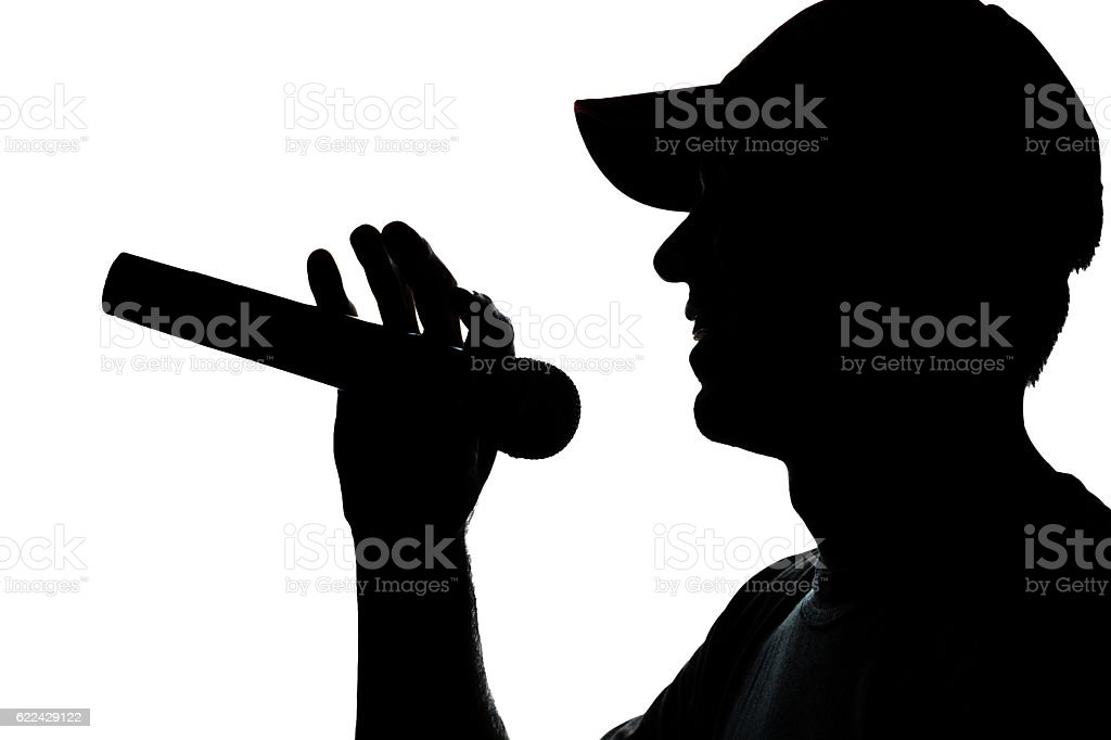Young man in cap singing into a microphone stock photo