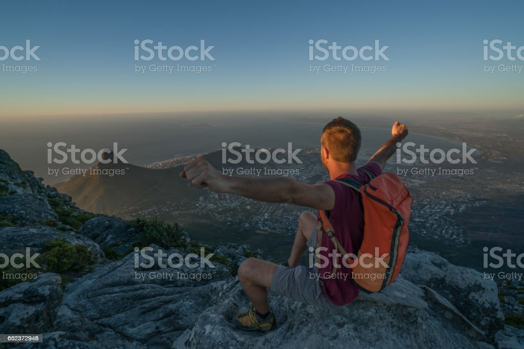 Young man in Cape Town on top of mountain arms outstretched stock photo