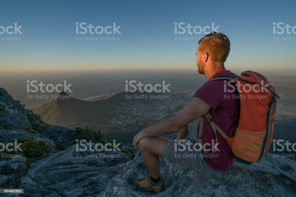 Young man in Cape Town on top of mountain looking at view stock photo