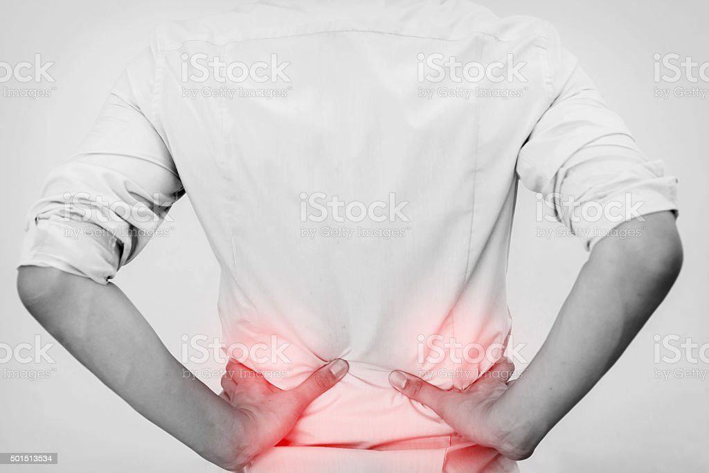 Young man in casual office shirt having hip pain stock photo