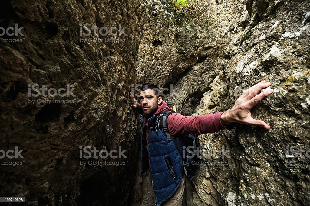 Young man in cave stock photo