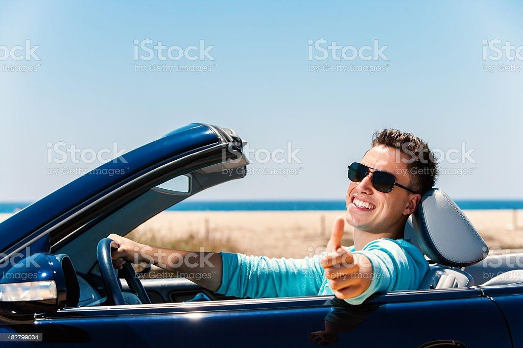 Jeune homme en Décapotable faire les pouces en l'air. photo libre de droits