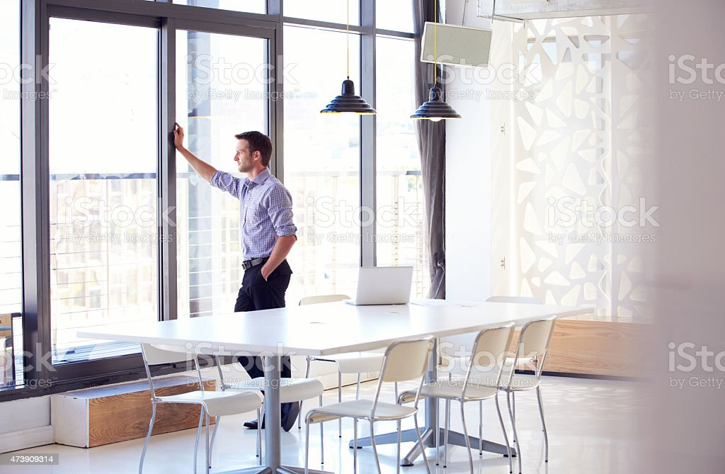 Young man in empty meeting room looking out of window stock photo