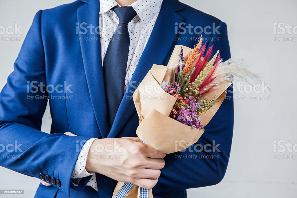 Young man in fashionable suit holding hipster hand-made bouquet stock photo