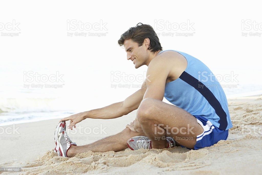 Young Man In Fitness Clothing Stretching On Beach stock photo