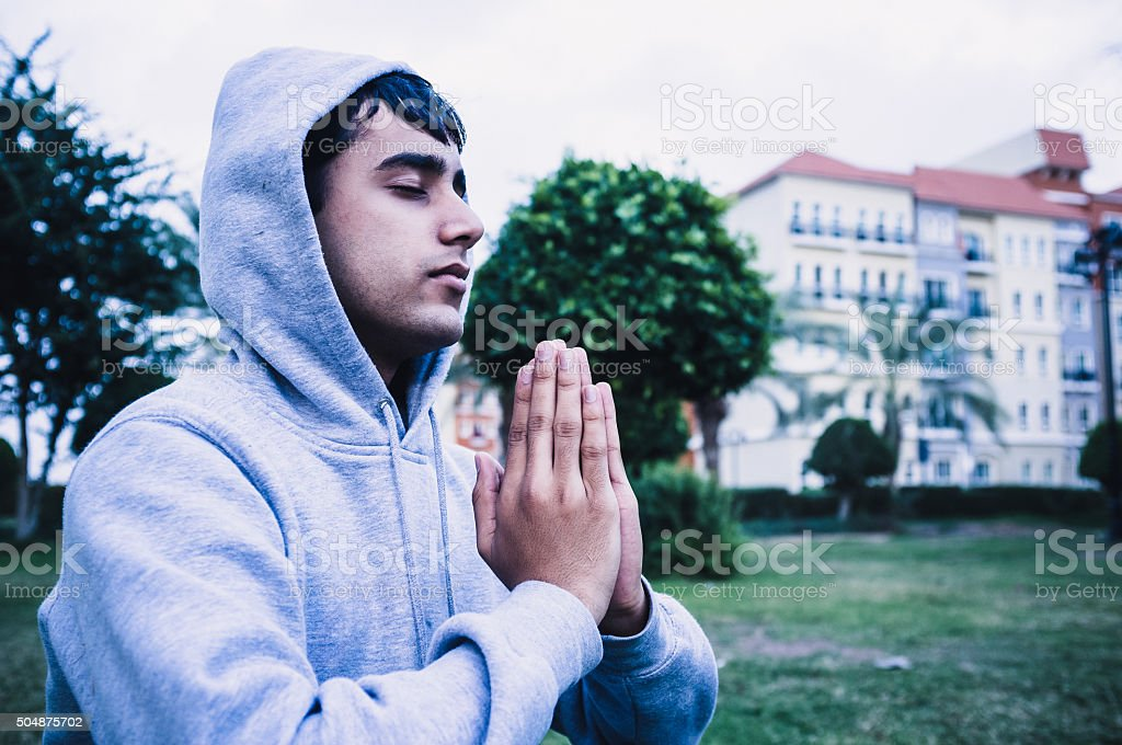 Young man in focused yoga position stock photo
