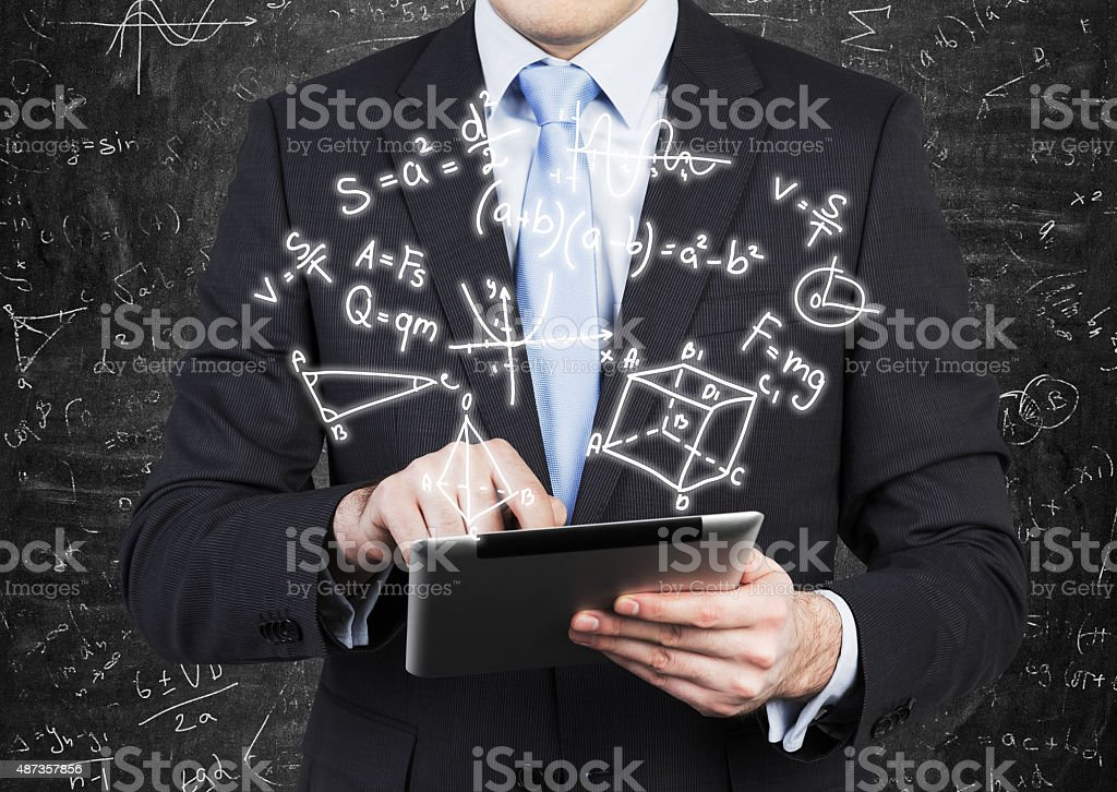 Young man in formal suit is holding a tablet stock photo