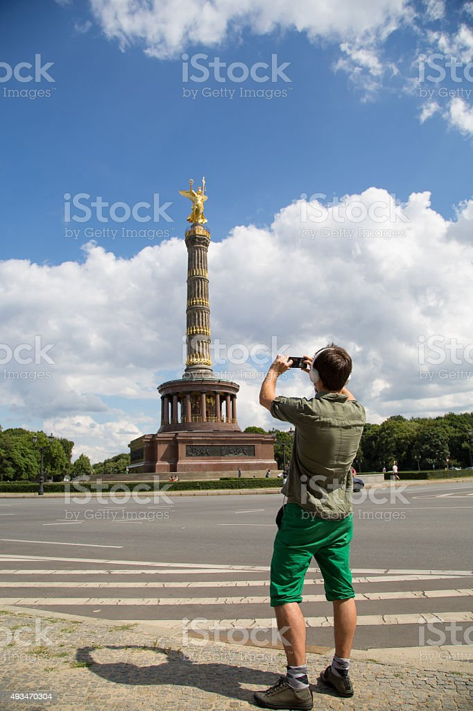 Young man in front of Victory Column in Berlin stock photo