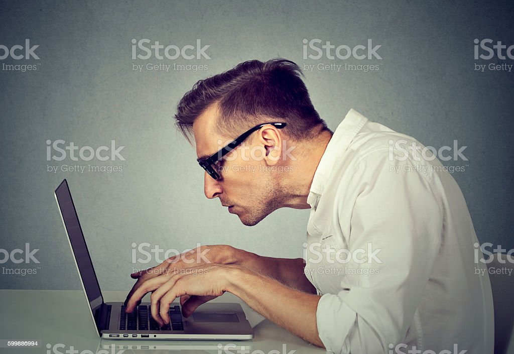 young man in glasses working on computer stock photo