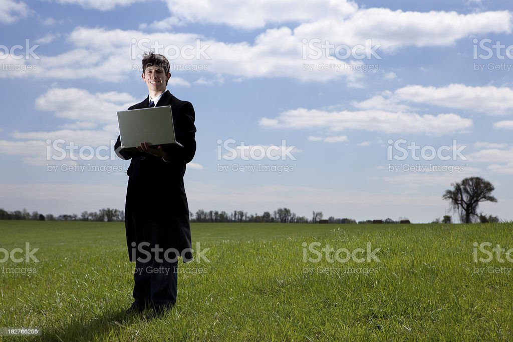 Young Man in Green Field with Laptop royalty-free stock photo