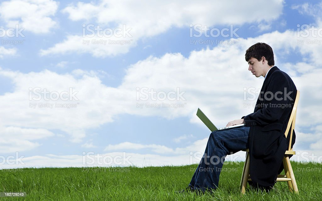 Young Man in Green Field working on Laptop royalty-free stock photo