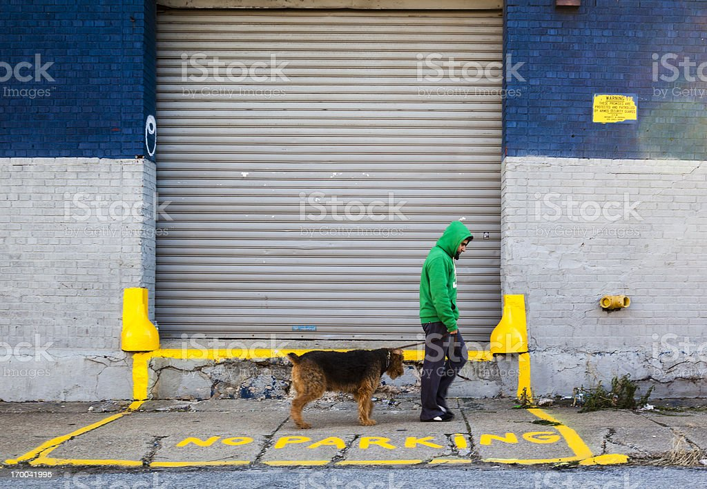 Young Man in Green Jacket Walks Dog in Brooklyn, New York stock photo