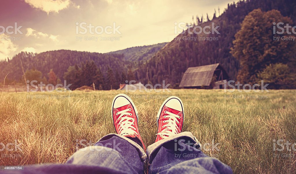 Young man in gumshoes and jeans have a rest on green grass in the...