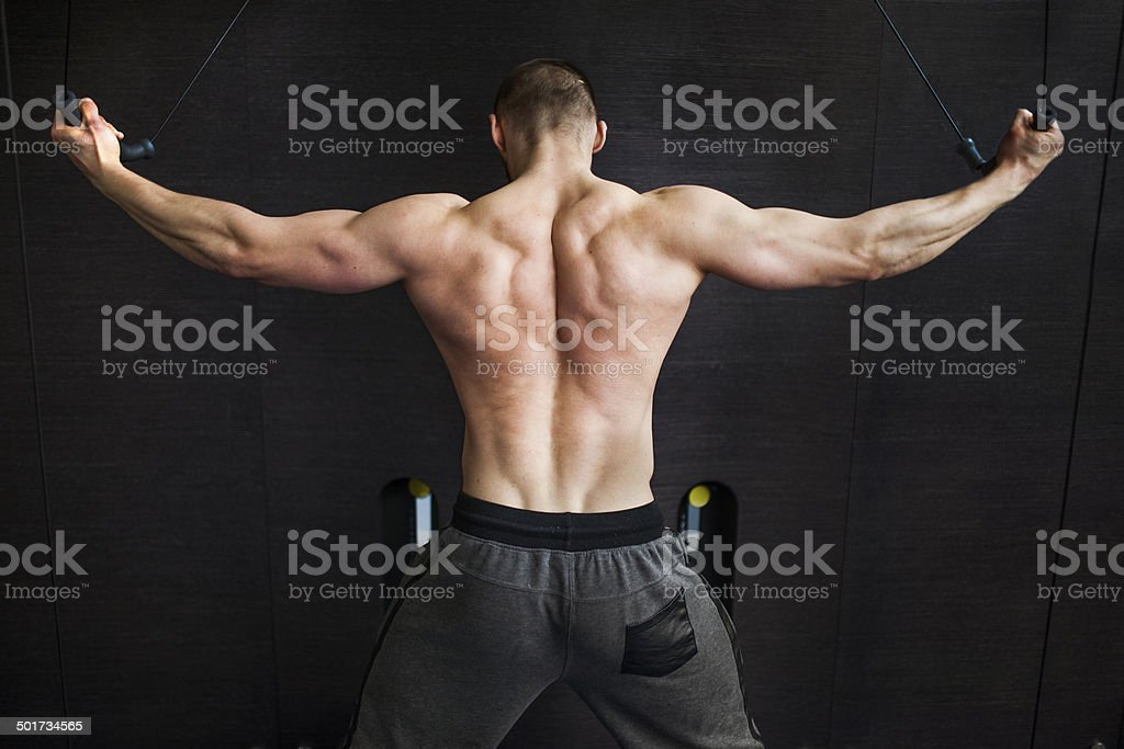 Young man in gym - cable multigym machine. stock photo