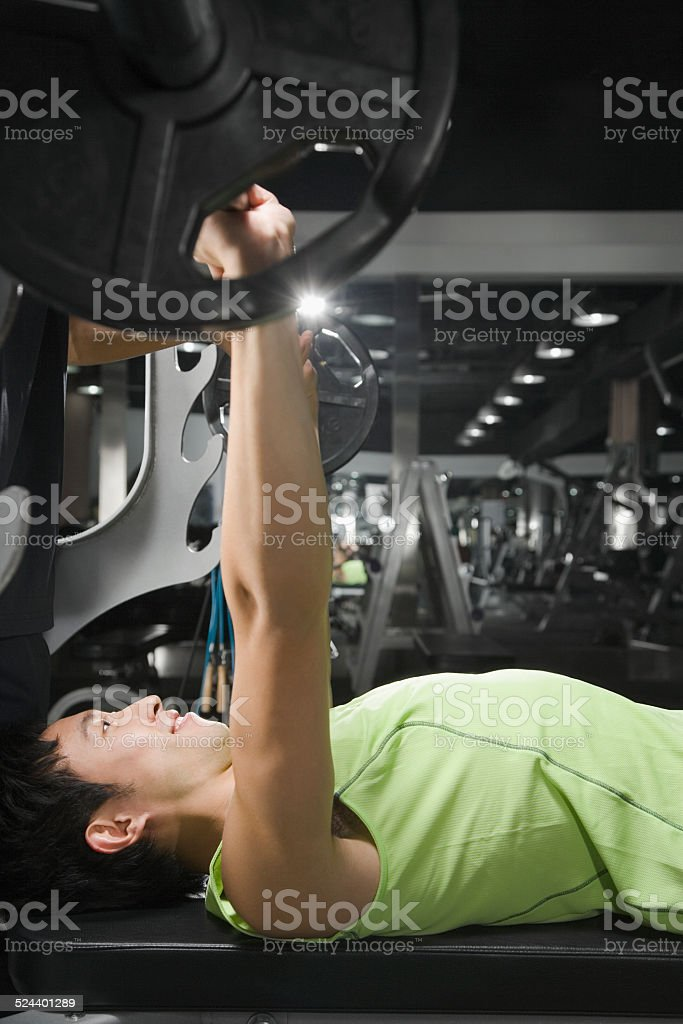 Young man in gym lifting weight, side view stock photo