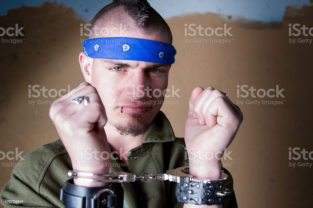 Young Man in Handcuffs with Big Smirk on His Face stock photo