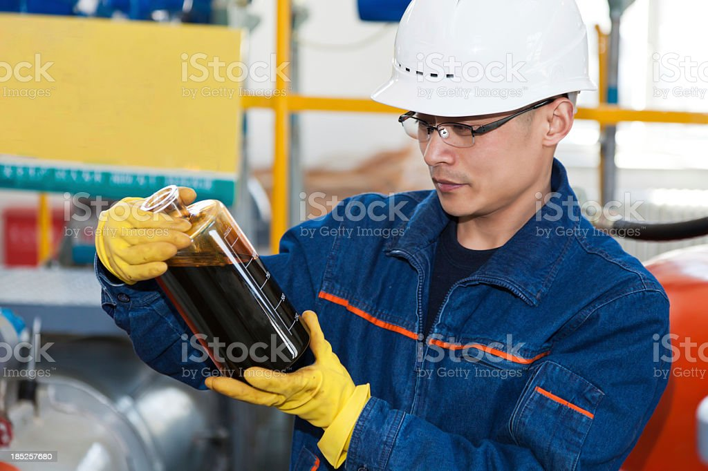 Young man in hard hat and gloves examining a bottle of oil stock photo