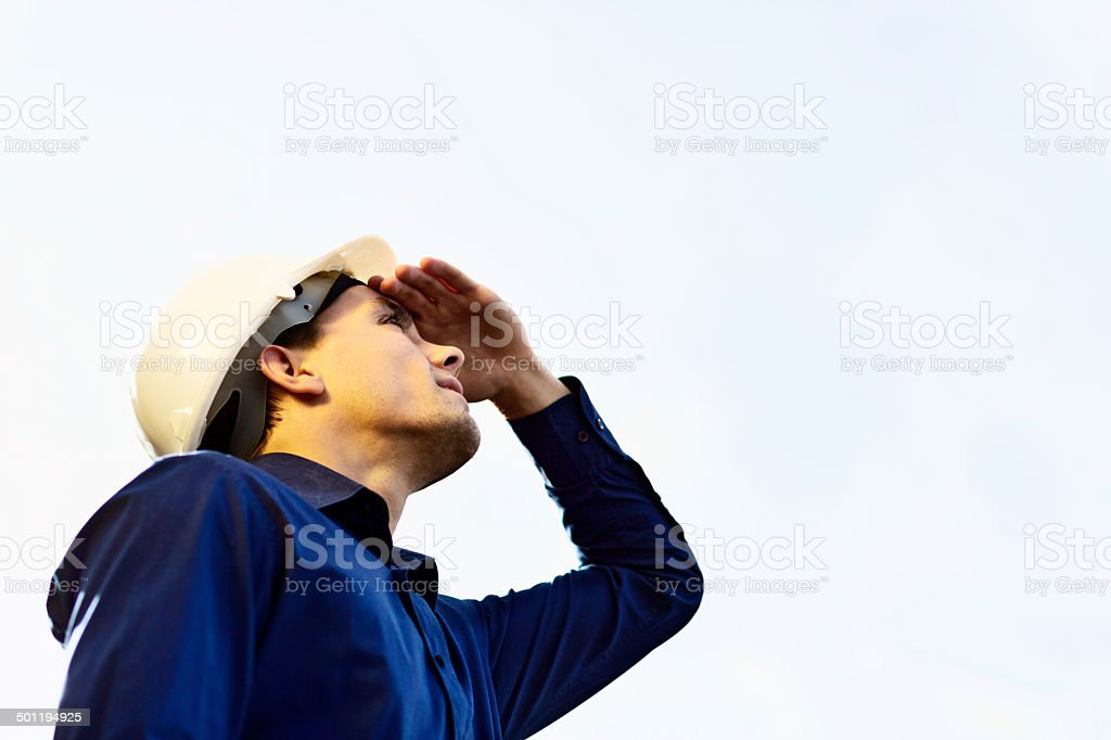 Young man in hard hat looks up, shading his eyes stock photo