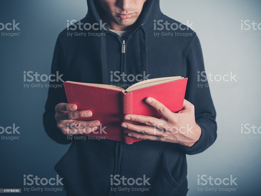 Young man in hooded top reading red book stock photo
