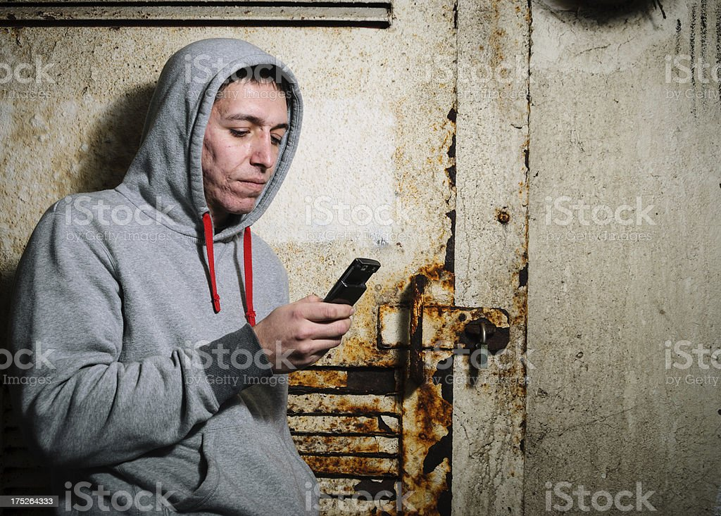 Young Man in Hooded Top Texting - Horizontal royalty-free stock photo