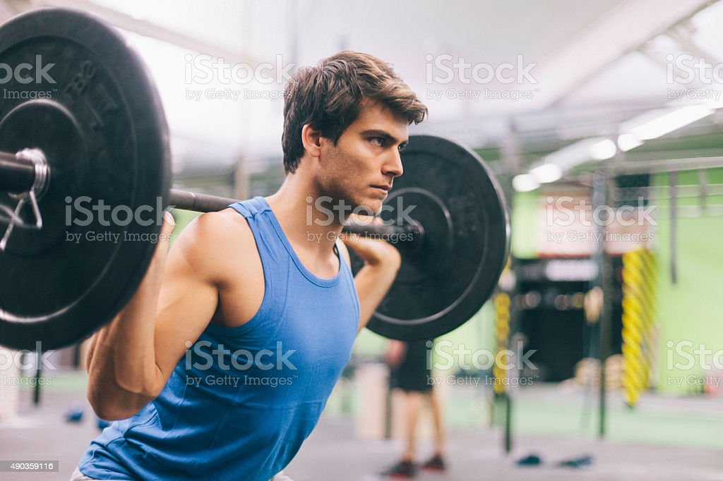 Young man in intensity training session lifting weights. stock photo