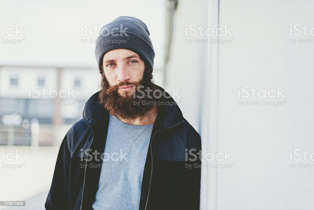 Young Man in Jacket and Bonnet Leaning on Wall stock photo