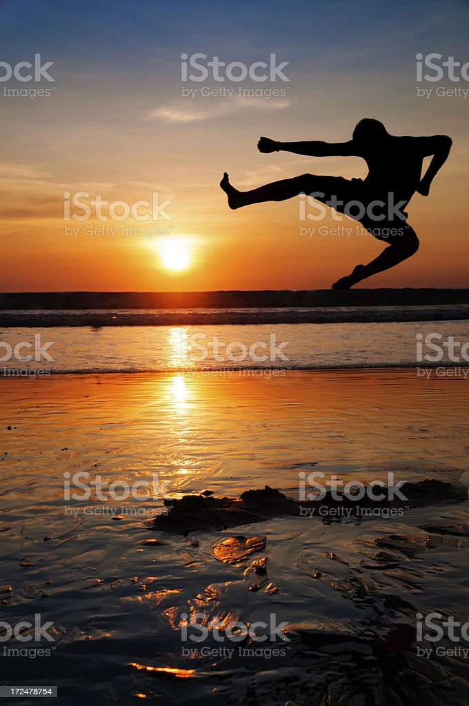 Young Man in Karate Jump on a Dark Seascape royalty-free stock photo