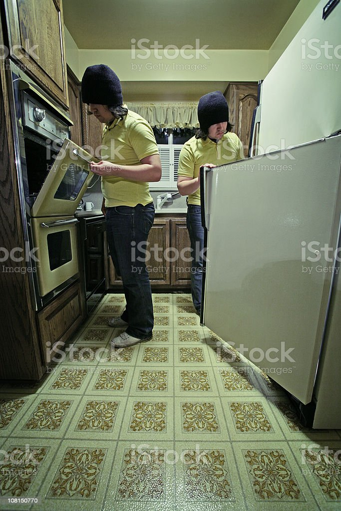 Young Man in Kitchen Looking at Fridge and Stove royalty-free stock photo