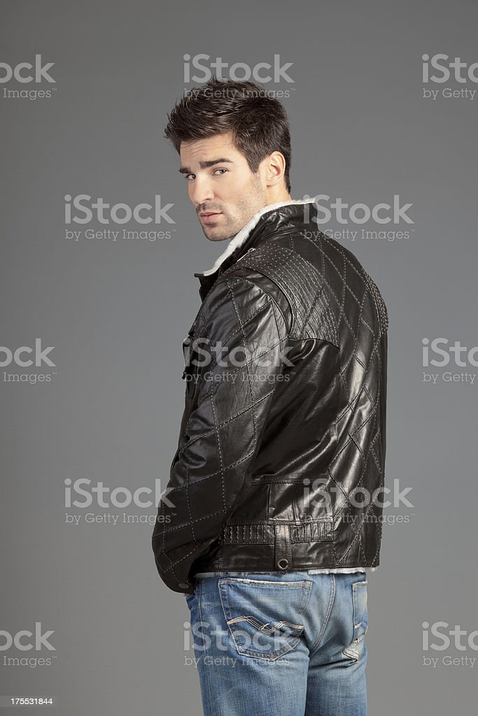Young man in leather jacket and jeans posing royalty-free stock photo
