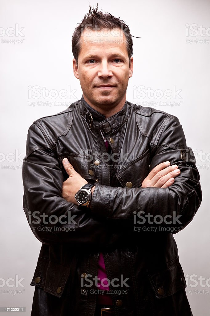 Young man in leather jacket with arms crossed (studio) stock photo