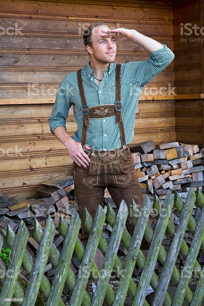 young man in lederhosen looking into the distance stock photo