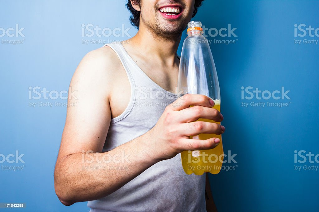 Young man in muscle vest with a bottle of drink royalty-free stock photo