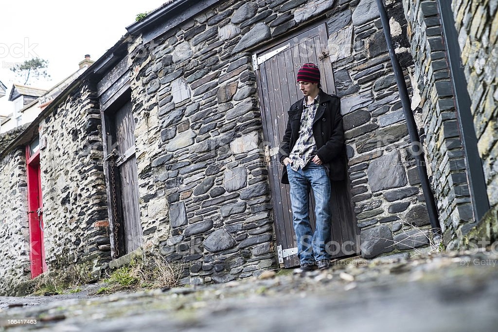 Young man in old cobbled street royalty-free stock photo