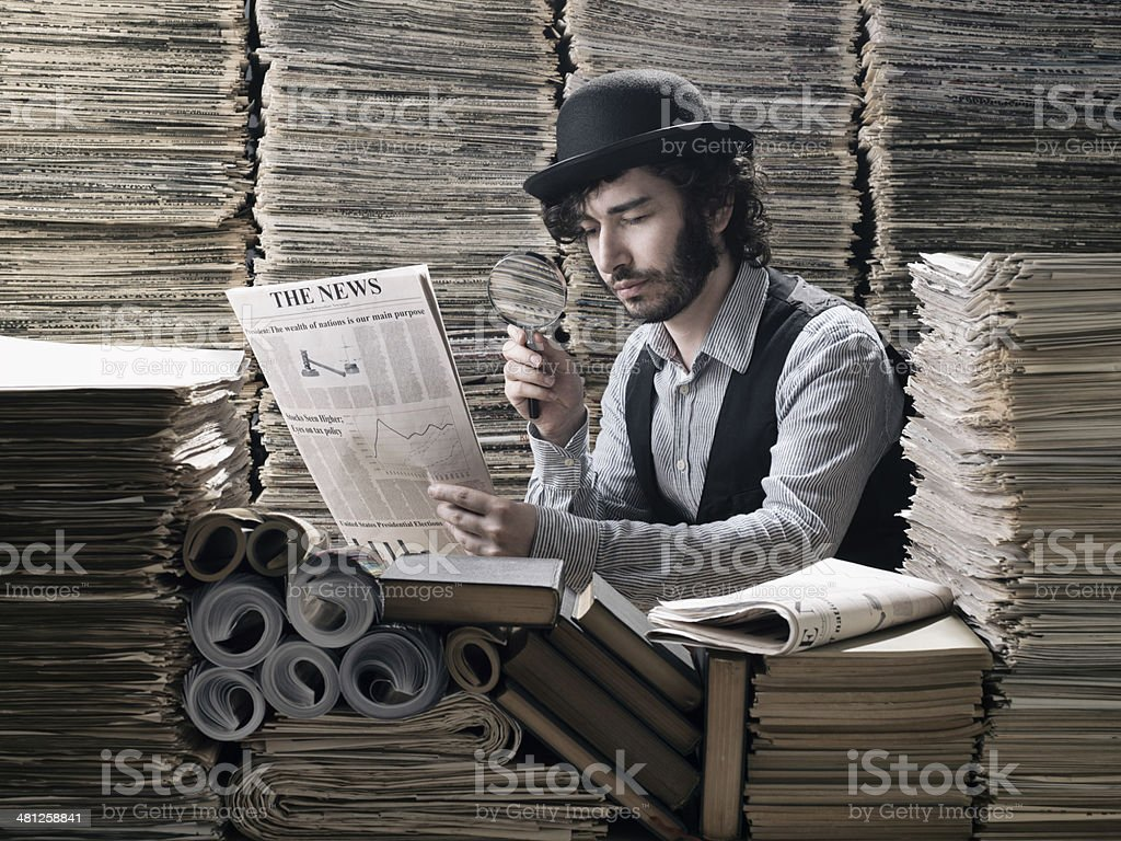 Young man in old fashioned costume doing research among newspapers stock photo