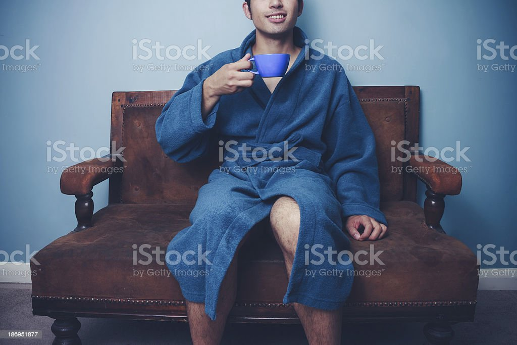 Young man in robe drinking coffee on sofa royalty-free stock photo