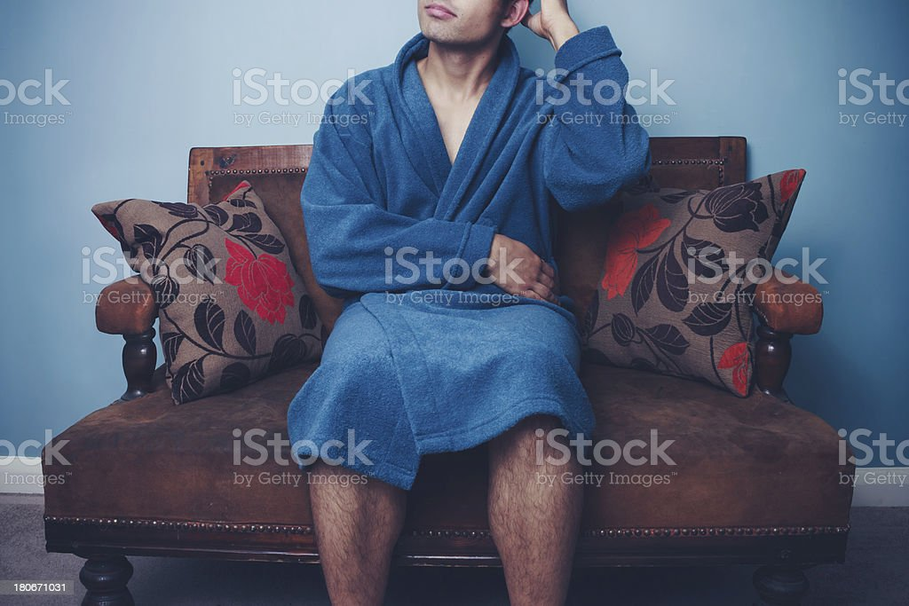 Young man in robe on sofa scratching his head royalty-free stock photo