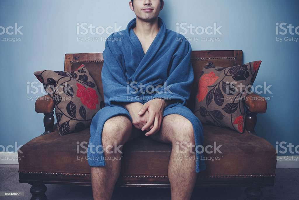 Young man in robe sitting on sofa royalty-free stock photo