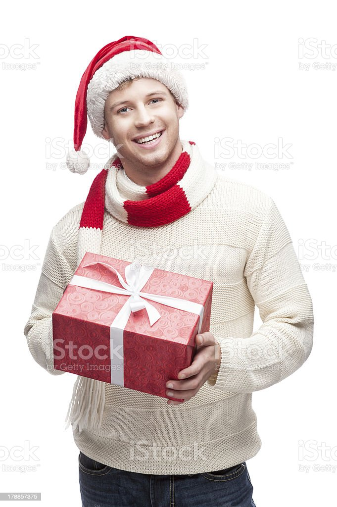young man in santa hat holding big red christmas gift royalty-free stock photo