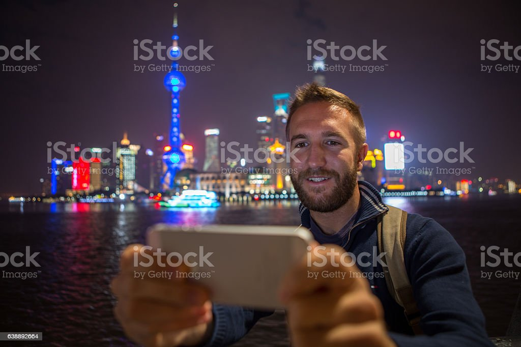 Young man in Shanghai takes selfie portrait at night stock photo