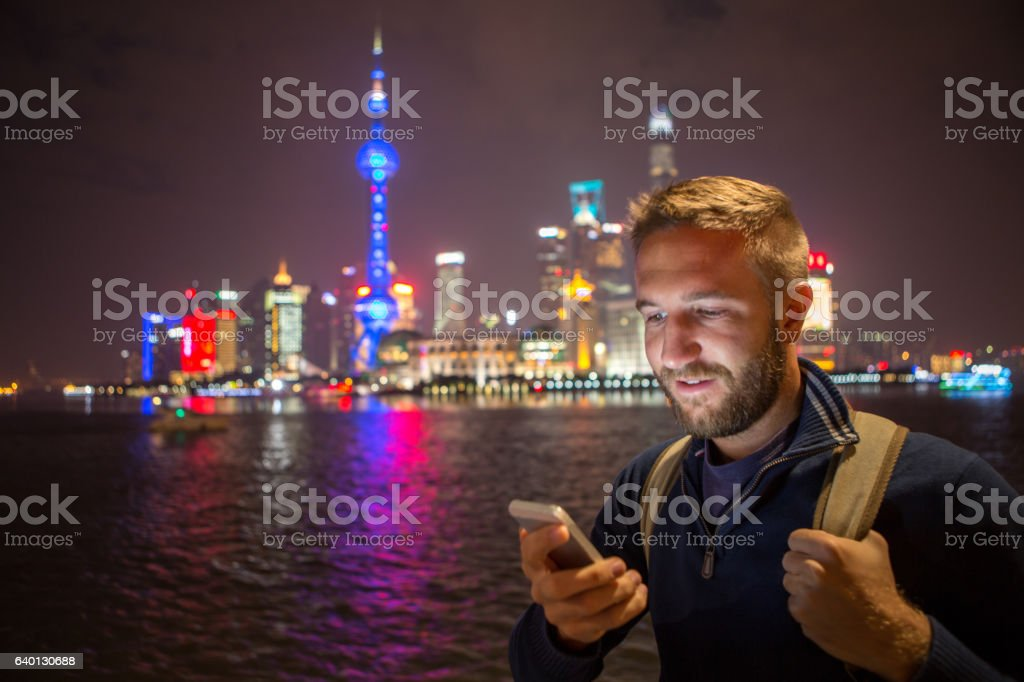 Young man in Shanghai text messaging on mobile phone, night stock photo