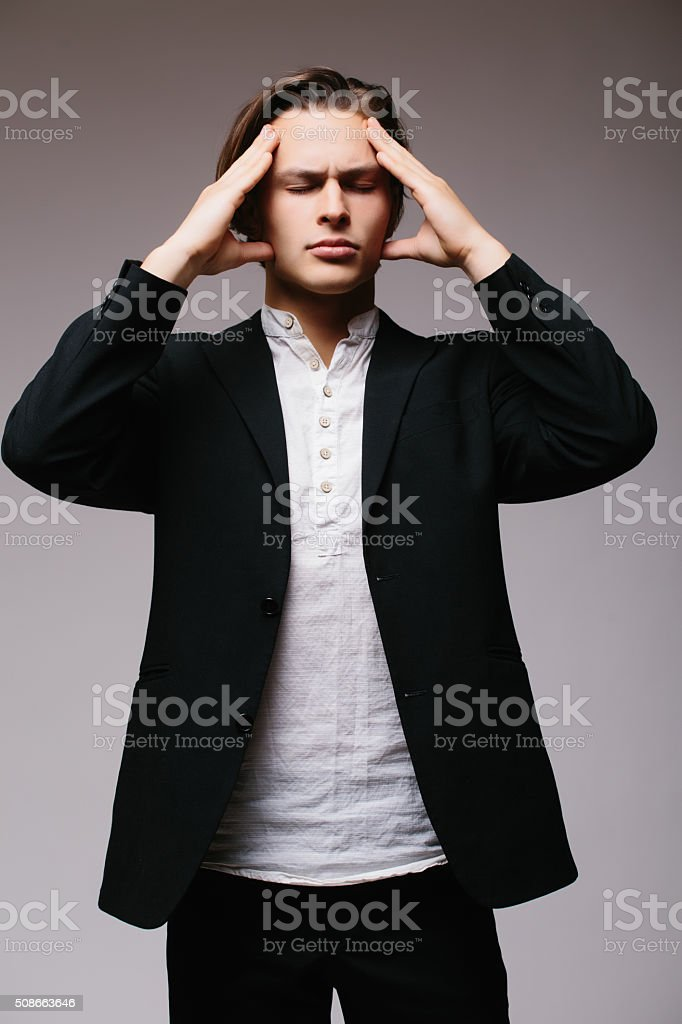Young man in shirt touching head and keeping eyes closed stock photo