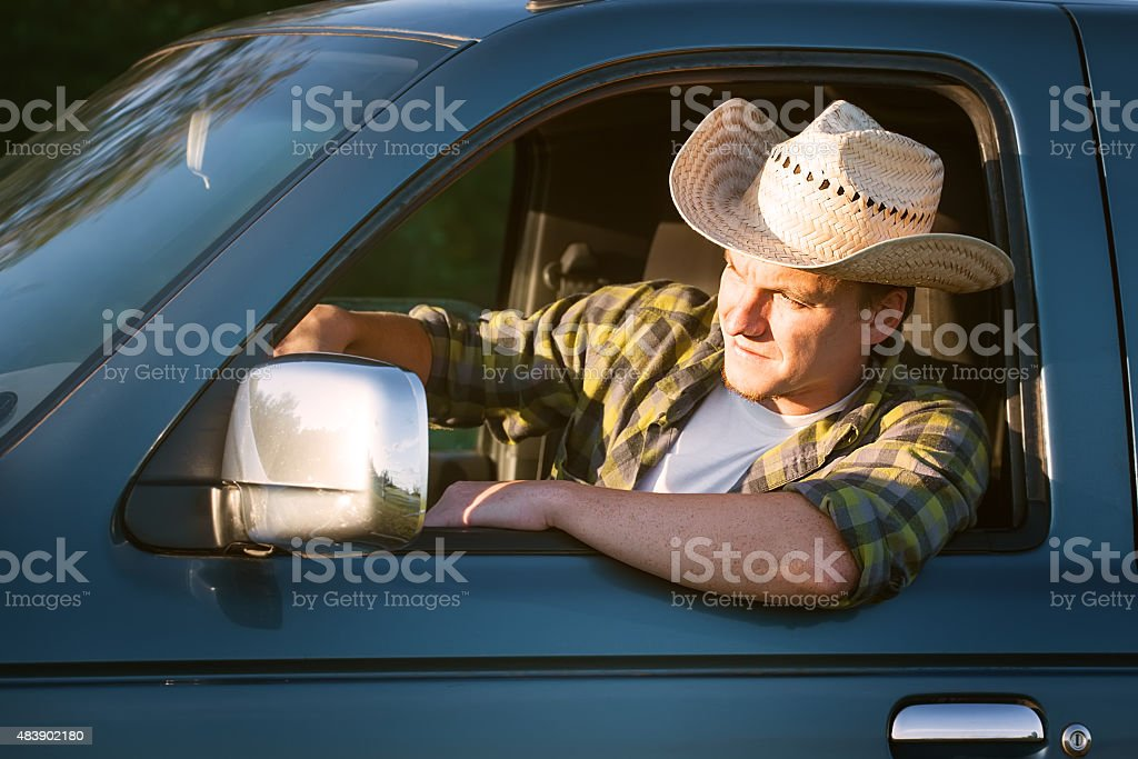 young man in straw hat driving truck stock photo