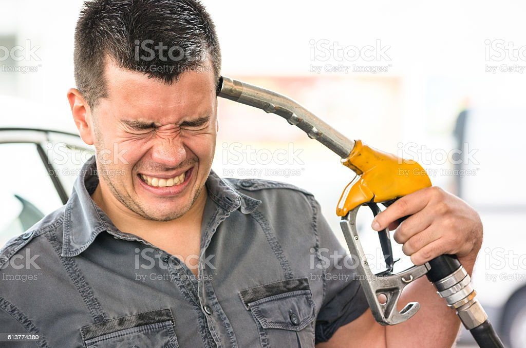 Young man in suicide position at gasoline fuel gas station stock photo