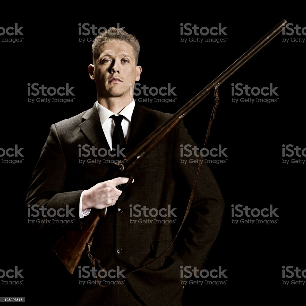 Young man in suit holding rifle stock photo