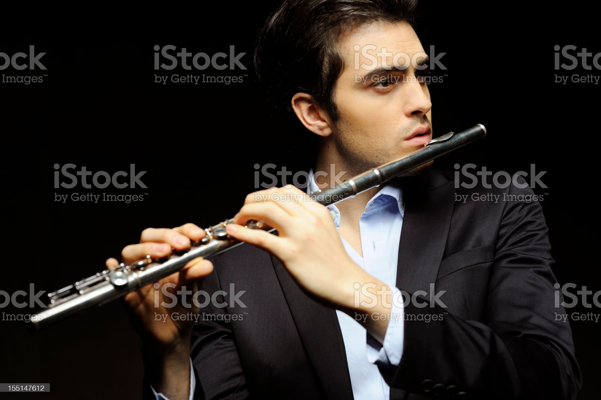 Young man in suit playing a flute royalty-free stock photo