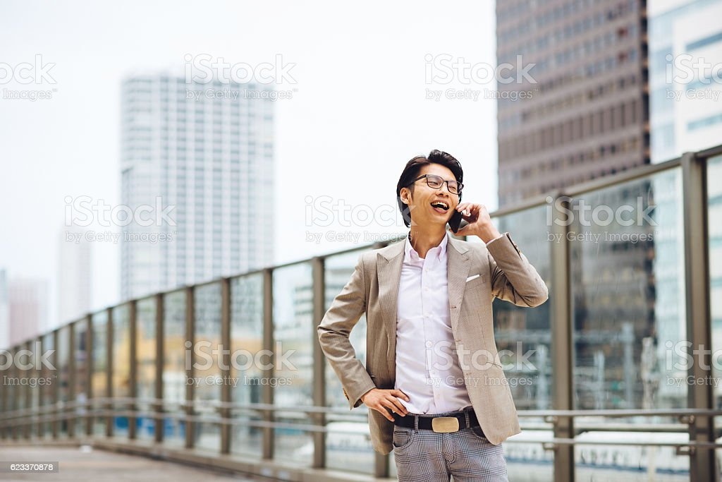Young man in suit, using phone for business stock photo